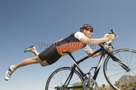 maennlicher radfahrer balancieren seinen magen auf
