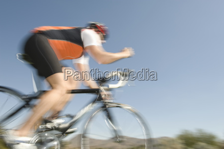 man riding bicycle against blue sky