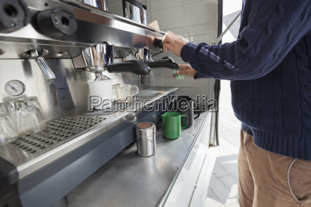 midsection of man cleaning coffee machine