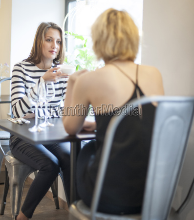 young female friends having coffee at