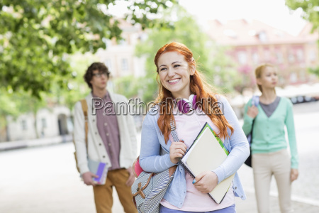smiling young female student with friends