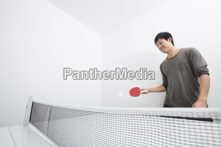 asian mid adult man playing ping