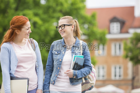 happy young female college friends walking