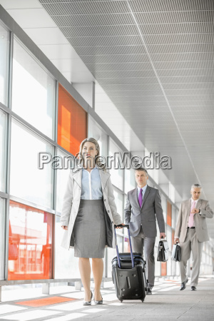 full length of businesspeople with luggage