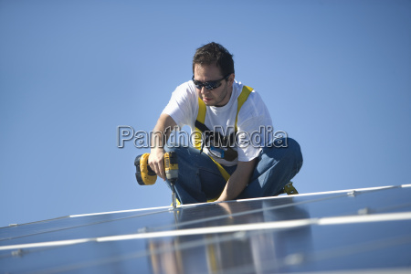 engineer drilling solar panel against blue