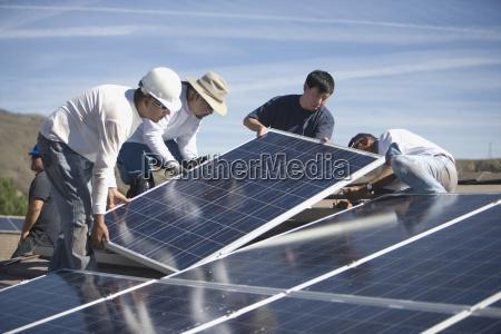 ingenieure setzen sonnenkollektoren auf dachterrasse