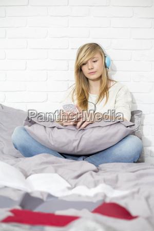 full length of teenage girl listening