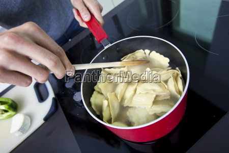 midsection of man cooking pasta on