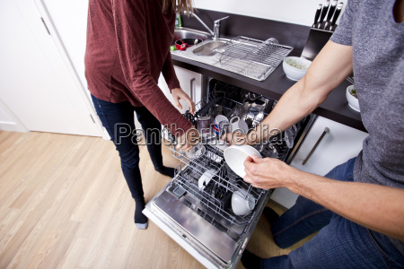 caucasian couple loading dishwasher together in