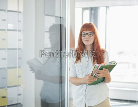portrait of confident businesswoman holding files