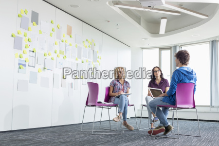 businesspeople discussing in creative office space