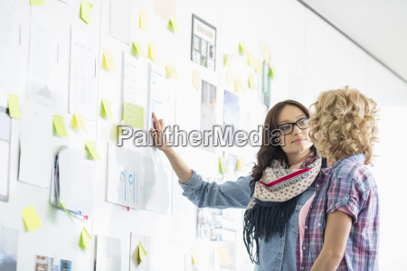 creative businesswomen discussing over papers stuck