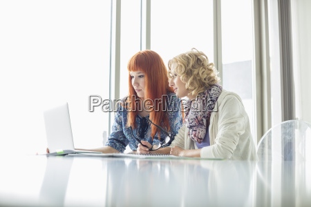 creative businesswomen working on laptop together