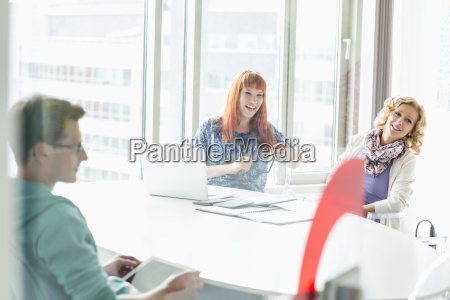 happy businesspeople sitting at desk in