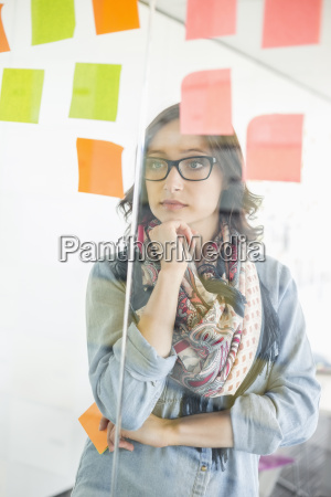 creative businesswoman reading sticky notes on