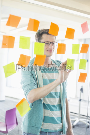 smiling businessman reading sticky notes on