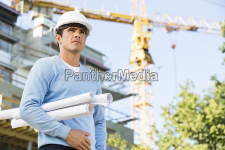 male architect holding rolled up blueprints