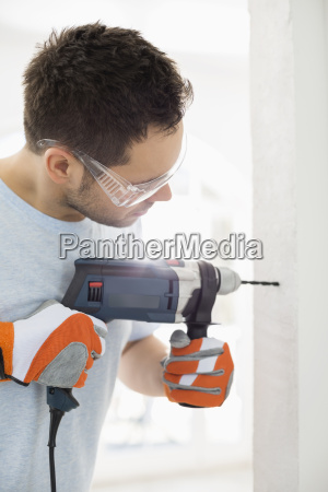 mid adult man drilling in wall