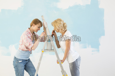 side view of female friends painting
