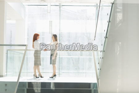 full length of businesswomen shaking hands