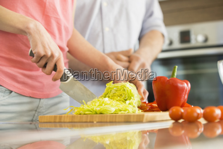midsection of woman chopping vegetables in