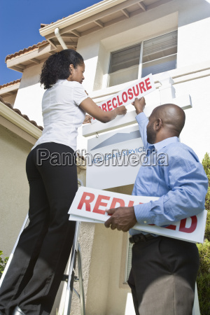 two people putting up notice outside