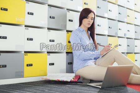beautiful businesswoman using laptop while writing