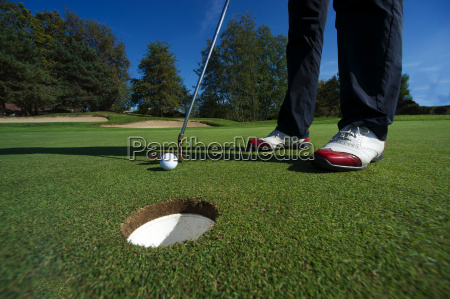 close up of person putting golf