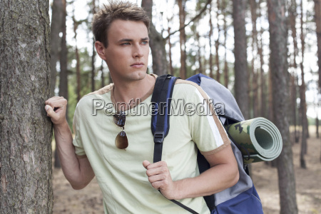 handsome young man with backpack hiking