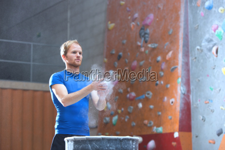 confident man dusting powder by climbing