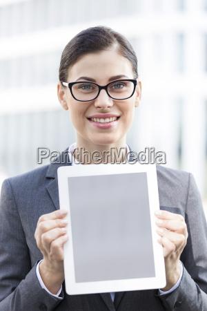 portrait of happy businesswoman showing digital