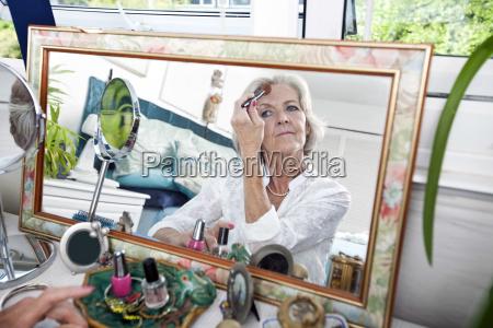 spiegelreflexion der aelteren frau die blusher