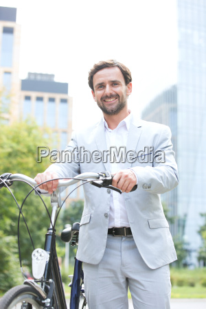 portrait of happy businessman holding bicycle
