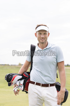 portrait of confident man carrying golf
