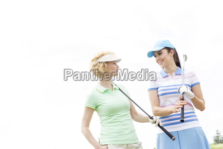 happy female golfers looking at each