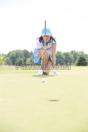 young woman aiming ball while kneeling