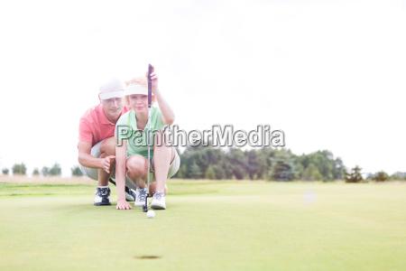 man assisting woman aiming ball on