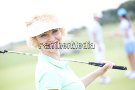 portrait of happy female golfer holding