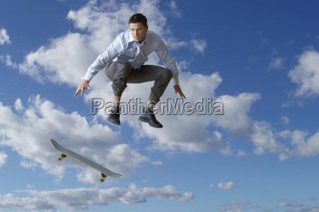 junge unternehmer durchfuehrung skateboarding trick in