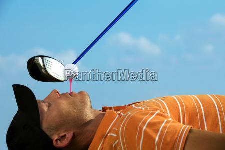 man balanciert golfball auf t stueck