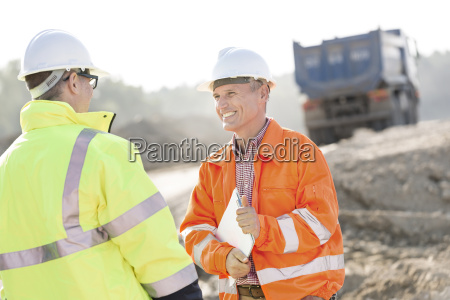 happy engineer discussing with colleague at