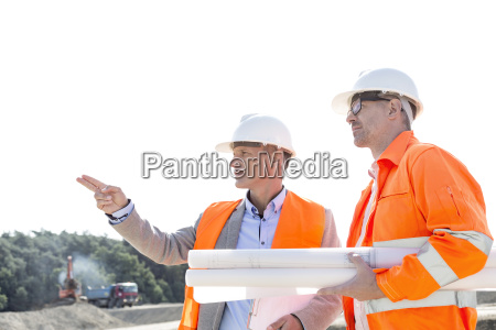 male engineers discussing at construction site
