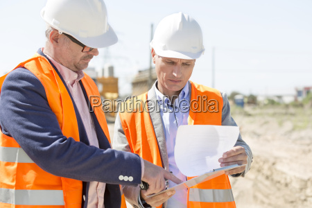 engineers examining documents on clipboard at