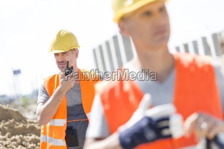 middle aged male worker using walkie