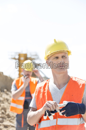 thoughtful worker standing at construction site