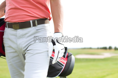 midsection of man carrying golf club