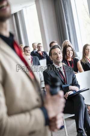 midsection of public speaker with business