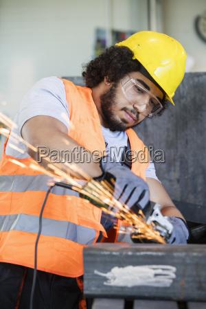 junge arbeiter in schutzkleidung schleifen metall