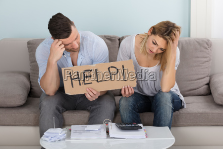 worried couple holding help sign while