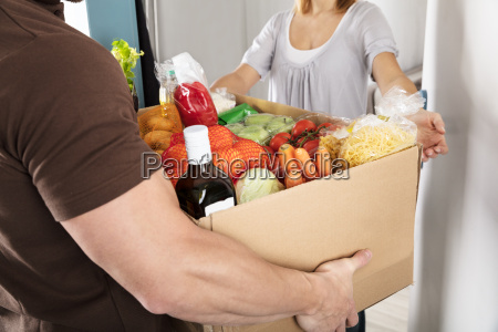 delivery man giving grocery box to